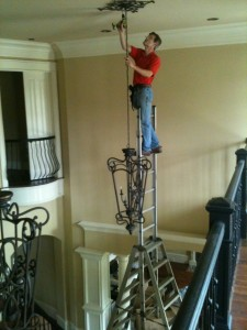 Chandelier installation on ladder
